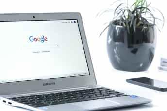 grey samsung laptop turned on beside black smartphone